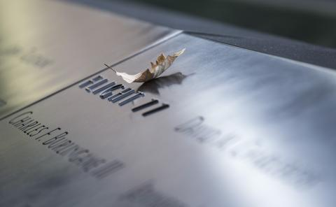 A swamp white oak leaf rests on a bronze parapet commemorating the Flight 77 victims at the south pool of the 9/11 Memorial.