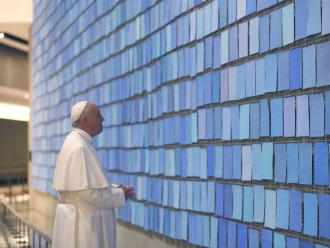 "Pope Francis views ""Trying to Remember the Color of the Sky on That September Morning"" by artist Spencer Finch. The pope is wearing a white outfit and cap as he looks at the dozens of blue tiles that make up the artwork."