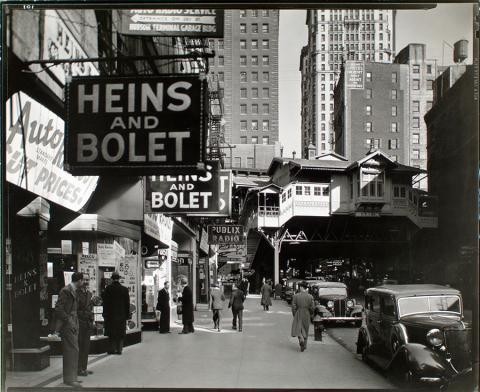 "A view shows ""Radio Row"" in Manhattan in 1936. Signs line storefronts. An elevated subway station is seen in the background."