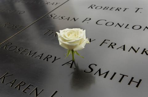 A white rose stands at the name of Rosemary Smith on the 9/11 Memorial.
