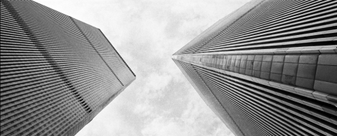 This old, black-and-white photo of the World Trade Center shows the Twin Towers from below on the plaza.