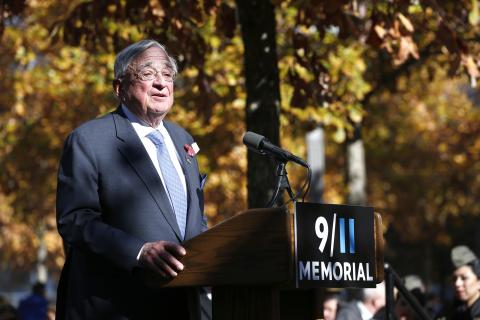 John E. Zuccotti wears a suit and tie as he speaks at a podium on the 9/11 Memorial.