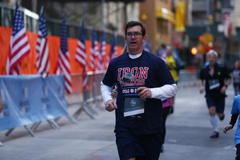 "A man in an ""Iron Workers"" T-shirt runs the course at the 9/11 Memorial & Museum 5K Run/Walk and Community Day."