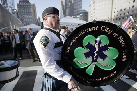 Members of the FDNY Emerald Society Pipes and Drums band play at the 9/11 Memorial during an event. White tents and groups of people are visible in the background.