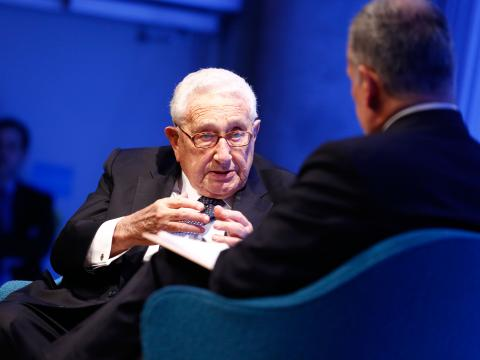 Former U.S. Secretary of State Henry Kissinger gestures as he speaks with Clifford Chanin, the executive vice president and deputy director for museum programs.