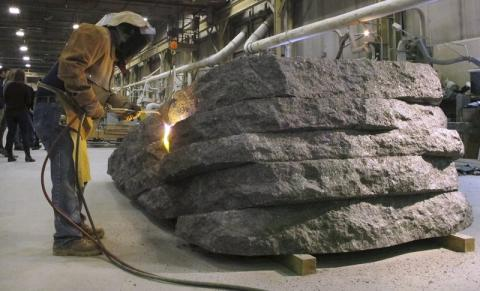 A masked worker from Rock of Ages uses a blowtorch to fuse a granite monolith for the 9/11 Memorial Glade.