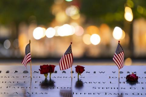 Three, small American flags and several red roses have been placed as tributes at the names of victims on the 9/11 Memorial.