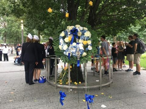 A white, yellow, and blue wreath laid by Blue Star Mothers stands next to the Survivor Tree at the Memorial.