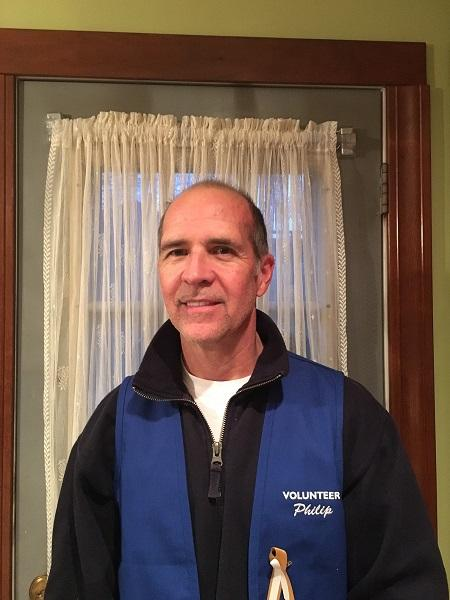 Port Authority employee Philip Caffrey poses for a photo in a blue volunteer vest.