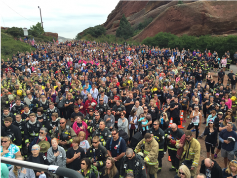 Hundreds of people put their right hands on their heart in a view over the Colorado Memorial Stair Climb on a cloudy day. Many first responders in the crowd are dressed in bunker gear and other uniforms.