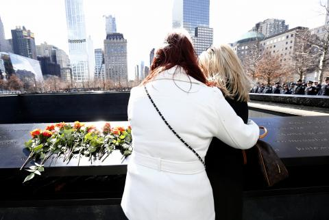 Two women, one in a white jacket and the other in a black jacket, embrace as they view a name at the Memorial. Flowers have been placed on the bronze parapet where the names are inscribed.