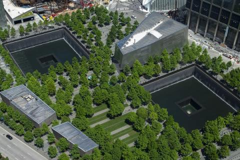 An aerial view of the 9/11 Memorial shows the twin reflecting pools, the Museum pavilion, and the plaza's many trees and pathways.