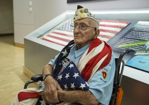 John Seelie, a U.S. Army veteran and Pearl Harbor survivor, holds an American flag as he sits in a wheelchair during a visit to the 9/11 Memorial Museum.
