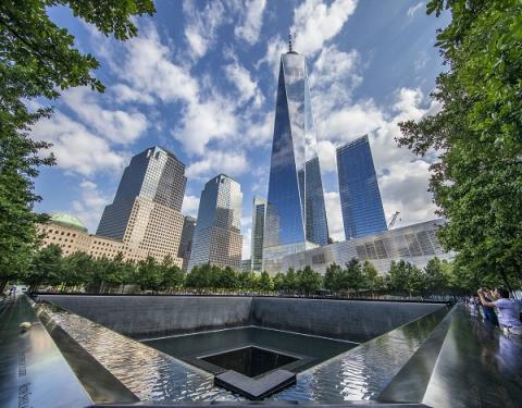 One World Trade Center towers over the south pool of Memorial plaza on a partly cloudy day.