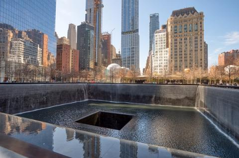 A view over the south pool of the 9/11 Memorial on a sunny day shows buildings reflecting in the water of the pool.