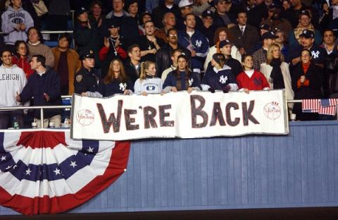 "Yankees fans hold a sign reading ""We're Back"" as they sit in the stands during a World Series game after 9/11."