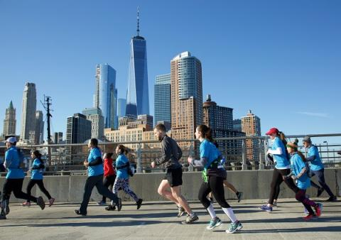 About a dozen runners are seen participating in the 9/11 Memorial & Museum 5K Run/Walk and Community Day. They are running on a concrete bridge with One World Trade Center and lower Manhattan behind them.