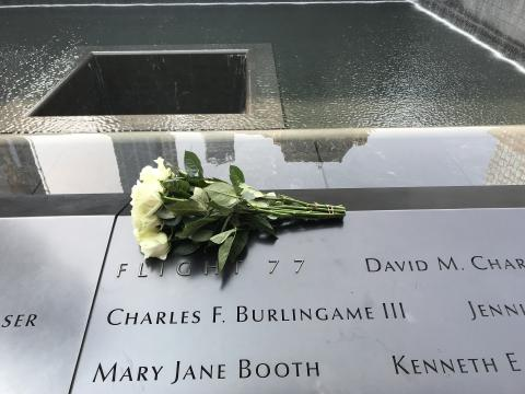 A bouquet of white roses sits at the section of the Memorial dedicated to the victims of Flight 77. The memorial pool can be seen in the background.