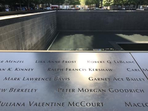 The names of Mark Lawrence Bavis and Garnet Ace Bailey are shown on a bronze parapet at the Memorial's south pool. Sunlight is reflecting on their names and the names of other victims.