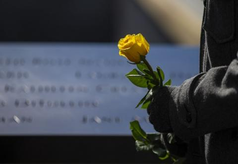 Only a person's gloved hands are visible as they hold a yellow rose beside names on the 9/11 Memorial.