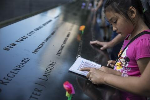 A girl stands at a bronze parapate etched with the names of victims. A woman's arm is seen pointing to a piece of paper the girl is reading.