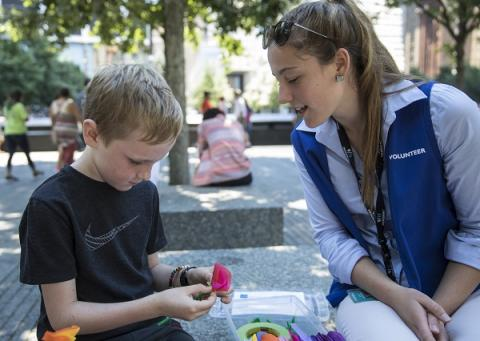 A young boy makes origami as a young woman in a volunteer vest watches on. The two are sitting on a bench at the Memorial as part of the Stories & Art program.