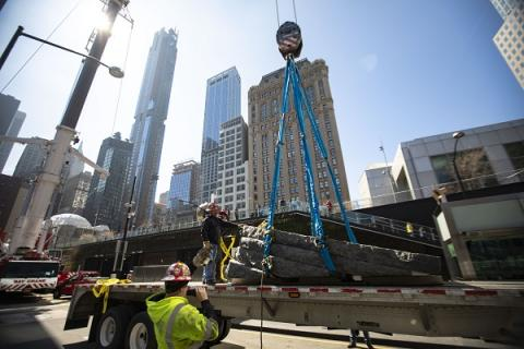 A 600-ton crane hoists a stone monolith to be placed at the 9/11 Memorial Glade on the Memorial plaza. Workers help position the monolith as it sits on the back of a flatbed truck.