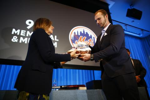 Mets first baseman Pete Alonso hands his 9/11 tribute cleats to 9/11 Memorial & Museum President and CEO Alice M. Greenwald onstage at the Museum auditorium.