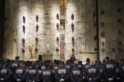 NYPD recruits stand in front of the slurry wall during a ceremony in the 9/11 Memorial Museum's Foundation Hall. The recruits are facing away from the camera as the watch a speaker onstage. Their jackets read NYPD in large letters.