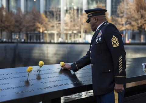 A man in a formal military outfit places a yellow rose at a victim's name on a bronze parapet at the 9/11 Memorial. Two other yellow roses have been placed at names nearby.