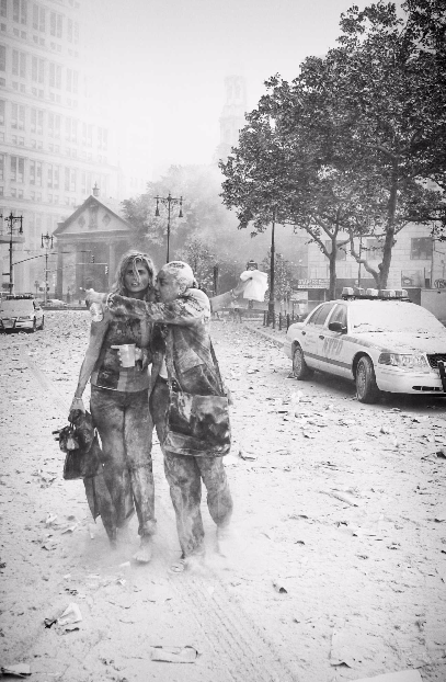 Joanne Capestro and a colleague are covered in dust as they flee the World Trade Center site on September 11. A cloud of dust covers the surrounding area, including the street and a police car.