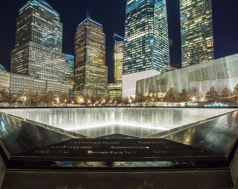 A reflecting pool of the 9/11 Memorial is seen illuminated at night. Surrounding buildings, including One World Trade Center, are lit up in the background.