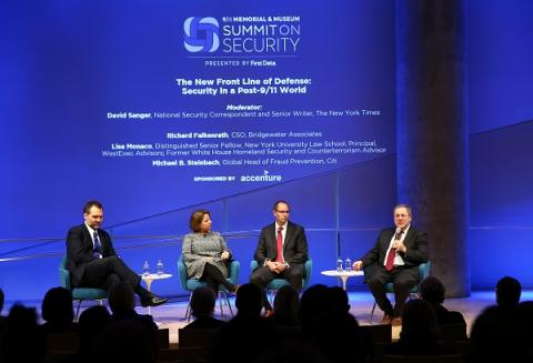 Three men in suits and a woman in a dress sit onstage at the Museum auditorium as they take part in a panel at the Summit on Security.