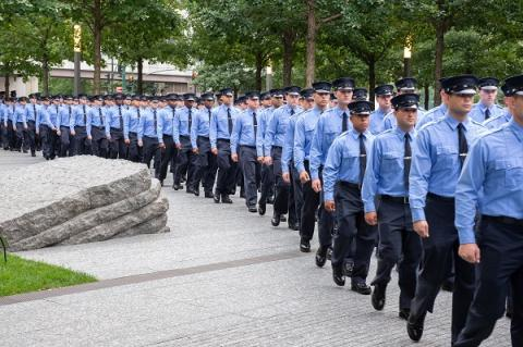 Dozens of FDNY probationary firefighters in formal, blue uniforms pass through the 9/11 Memorial Glade.