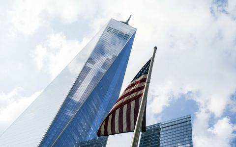An American flag flies over the 9/11 Memorial in this image looking up at One World Trade Center on a cloudy day. The clouds are seen reflecting off the glass of One World Trade Center.