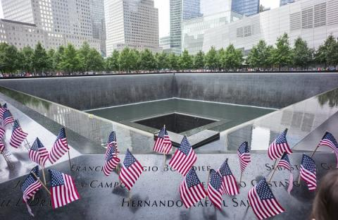 Dozens of small, American flags have been placed at names on the 9/11 Memorial in a sweeping photo of the south pool.