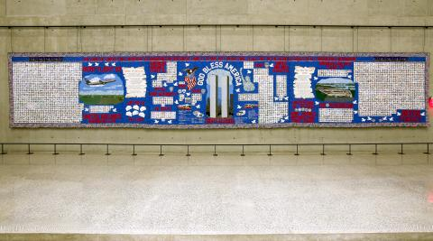 "A 60-foot-wide quilt titled America's 9/11 Victims Quilty is displayed at the Museum. The quilt features a latticework of pictures and names honoring the victims of the attacks. The center of the quilt includes a depiction of the Twin Towers with the words ""God Bless America."""