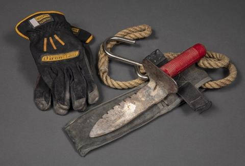 Tools and a pair of gloves belonging to George Torres of FDNY Squad 41 are displayed on a gray surface. The tools include a garden trowel with a red handle that Torres used to dig at Ground Zero.