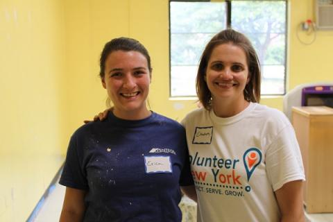 Two female volunteers embrace for a photo while painting a yellow-colored room at a Head Start learning center in Mount Vernon, New York.