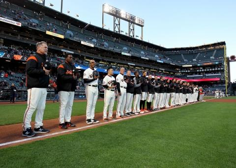 San Francisco Giants players hold their hats to their hearts as they pay tribute to those killed in the 9/11 attacks during a pre-game ceremony in AT&T Park.