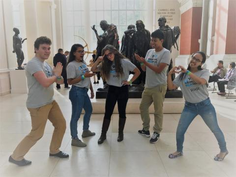 A group of 9/11 Museum ambassadors—two young men and three young women—strike a pose in the European sculpture gallery at the Metropolitan Museum of Art. Several sculptures stand behind them.