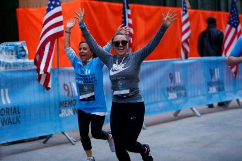 Two participants wave as they run along the route of the annual 9/11 Memorial & Museum 5K Run/Walk and Community Day.