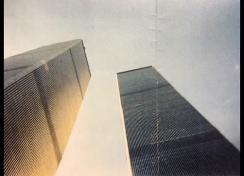 A photograph by Jeffrey Keating shows the Twin Towers from below on September 10, 2001. Sunlight shines on one of the towers. The other is cloaked in shadow.