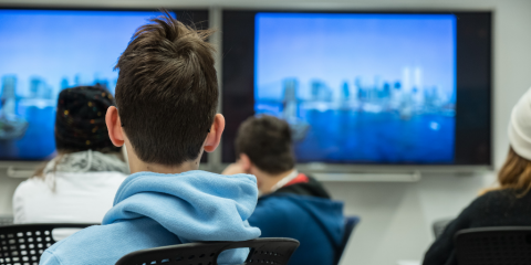 A student in a hoodie sit with his back to the camera in the Museums' Education Center. He and other students are watching television screens that are showing lower Manhattan.