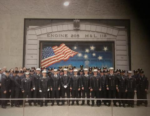 At the Museum's Tribute Walk, members of FDNY Engine 205 and Ladder 118 stand in front of a firehouse door painted in tribute to their fellow firefighters killed on 9/11. The painting depicts an American flag on a starry night.