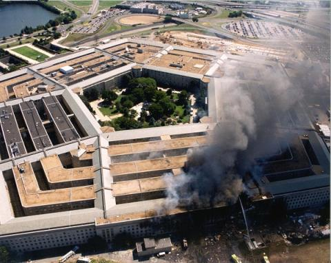 An aerial view of the entire Pentagon on 9/11 shows black and gray smoke rising from a large hole in the building.