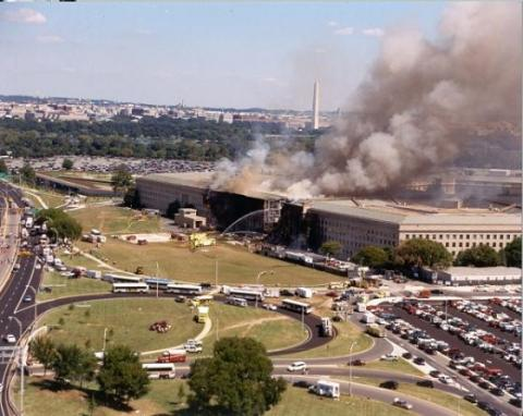 Thick smoke rises from the Pentagon on 9/11 as emergency responders converge on the scene. A charred hole can be seen where American Airlines Flight 77 was flown into the building. The skyline of Washington, D.C. is visible in the background.