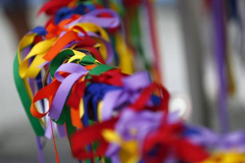 An abundance of rainbow-covered ribbons are loosely tied around a barrier in an act of memorialization.