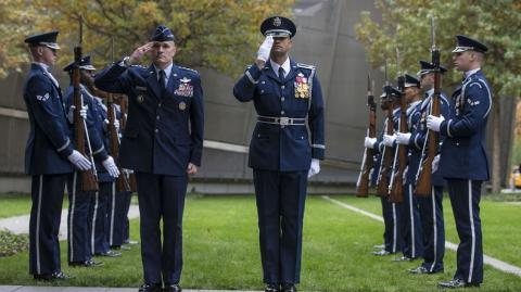 Members of the U.S. Air Force drill team outfitted in navy blue dress uniforms stand in two identical rows with rifles, while two members stand side-by-side in the foreground saluting away from the other members. In the background is the green lawn of the 9/11 Memorial plaza and trees that have begun to change color for the fall.