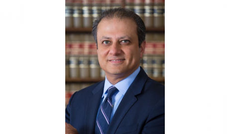 A headshot of Preet Bharara wearing a navy blue suit, standing in front of a wall of books.